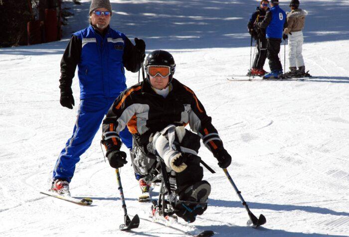 Sciatore disabile con il suo istruttore